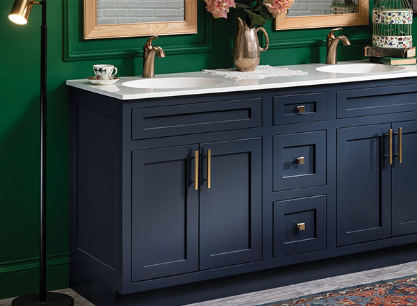 A bathroom vanity with blue cabinets and gold handles