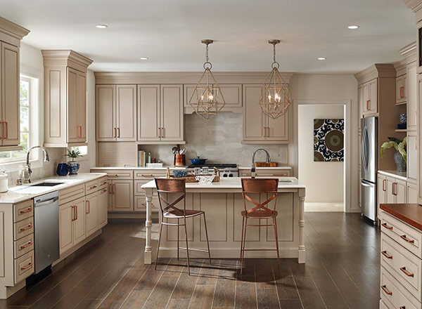 A kitchen with tan cabinets and copper handles
