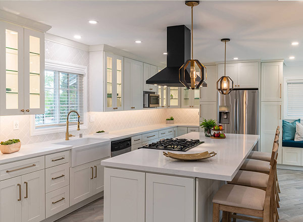 A kitchen with white cabinets and under-cabinet lighting