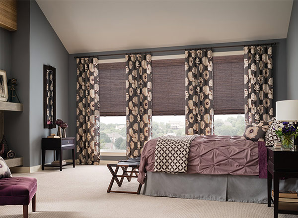 A bedroom with floor to ceiling windows covered by stylish blinds and drapes
