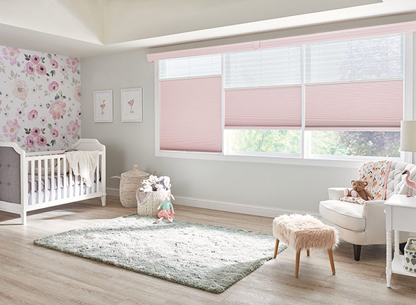 A baby girl's room with pink accents and blinds